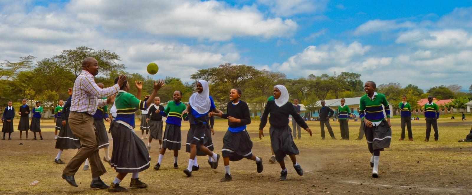 Volunteers coaching sports in schools in Tanzania play a ball game with students.